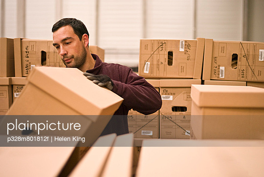 Man Packing Cardboard Boxes in Warehouse