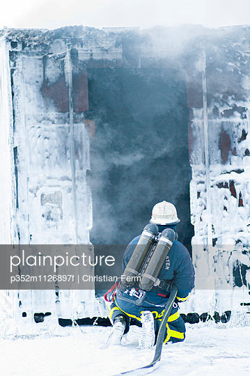 Sweden, Sodermanland, Firefighter kneeling by building covered with foam after fire