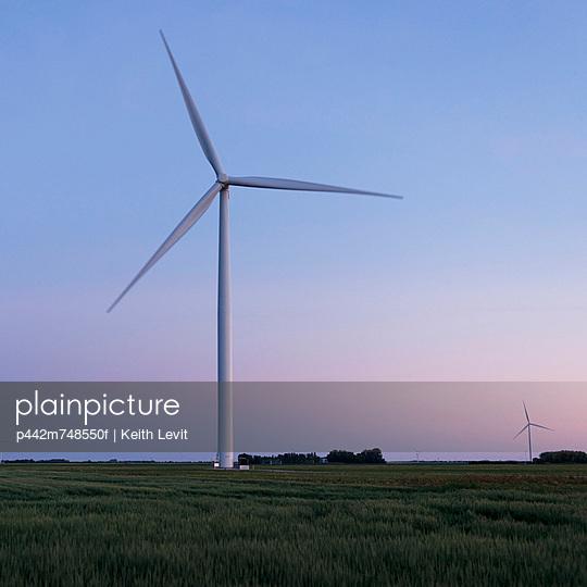 A Wind Turbine In A Field At Sunset; Manitoba Canada
