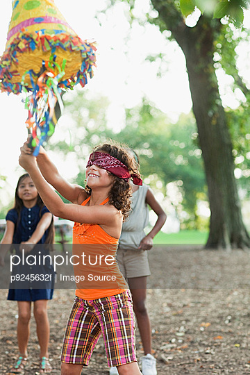 Girl at birthday party hitting pinata