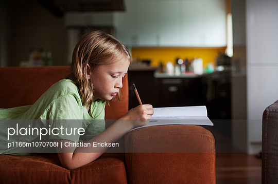Side view of boy writing in book while lying on sofa at home