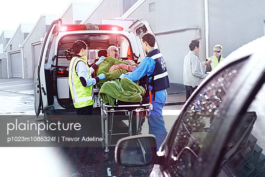 Rescue workers tending to car accident victim on stretcher at back of ambulance