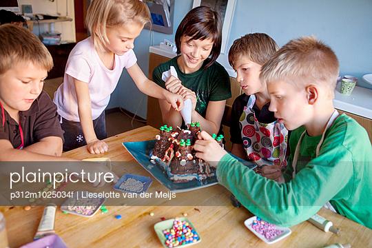 Children decorating cake