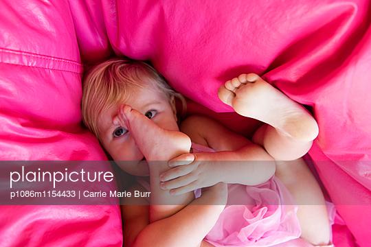 Kleines Mädchen spielt mit ihrem Füßen - p1086m1154433 von Carrie Marie Burr