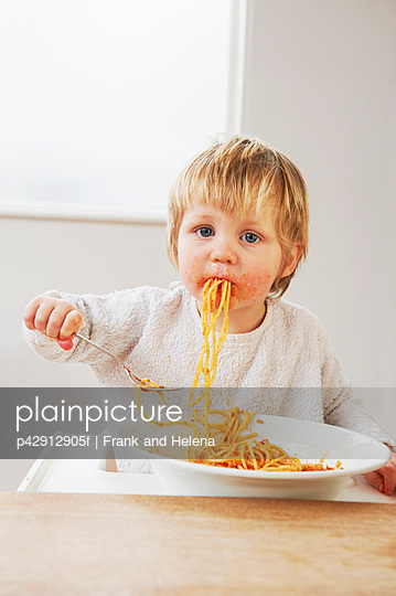 Messy baby boy eating spaghetti