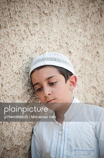 Sad Arabian boy leaning against the wall