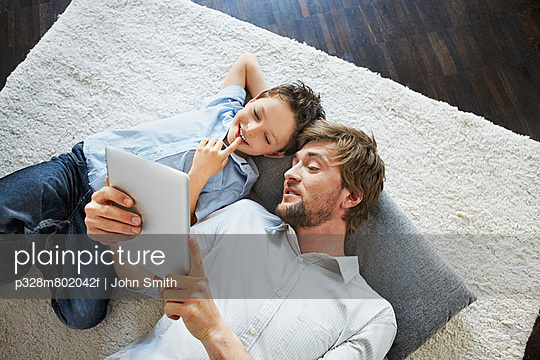 Happy young man and his son (8-9) lying on floor with digital tablet