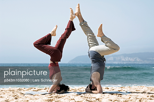 A man and woman practicing yoga on a rocky outcrop at North Curl Curl, one of Sydneys Northern Beaches. Sydney, N