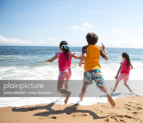 Back View of Children Running into the Sea