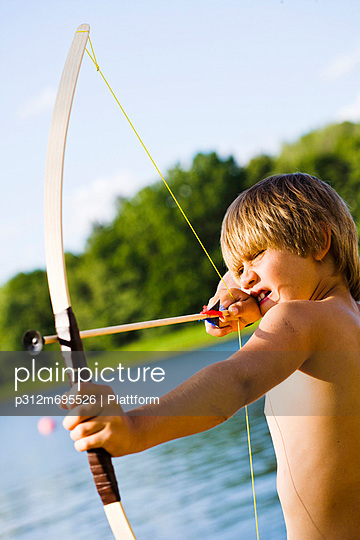Shirtless boy aiming bow and arrow