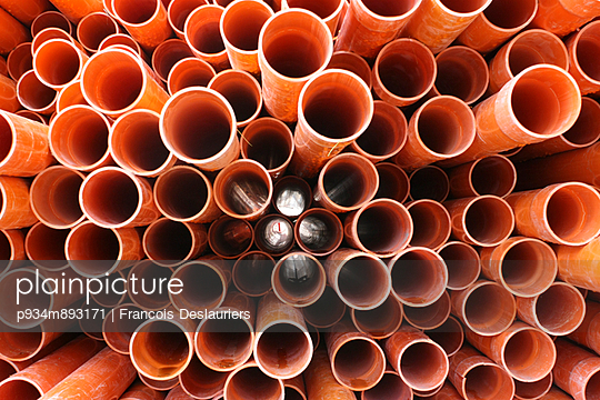 A pile of red pipes lying in a street