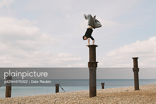 Parkour athlete experimenting with movement on beach, Sussex, United Kingdom