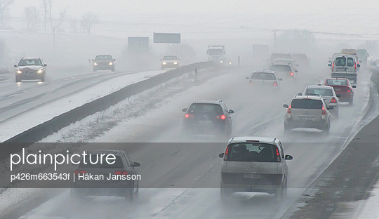 Vehicles moving on misty highway