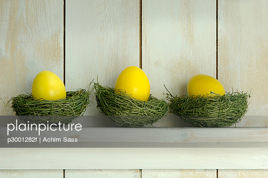 Yellow Easter eggs lying on shelf on grass