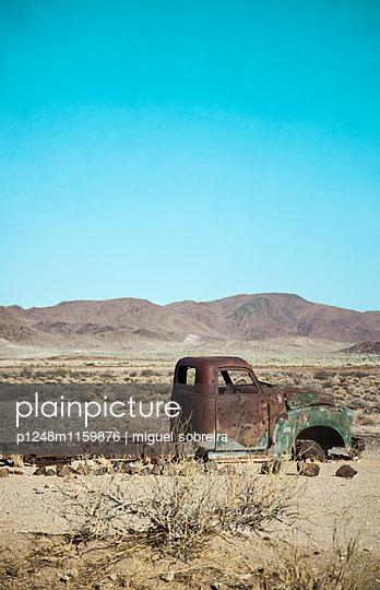 Verlassenes Schrottauto in der Wüste - p1248m1159876 von miguel sobreira