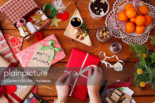 Directly above shot of hands tying ribbon on Christmas gift at wooden table