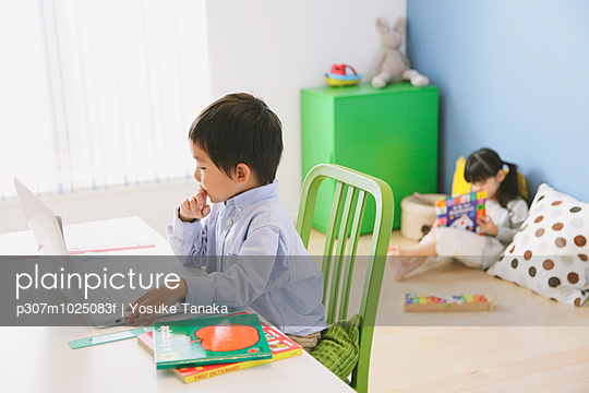 Elementary age boy doing his homework at his desk with his sister reading on the floor in the background