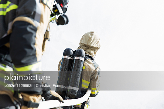 Sweden, Sodermanland, Two fire-fighters with oxygen tanks holding hose