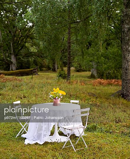 Tisch mit Blumenstrauß im Garten - p972m1160297 von Patric Johansson