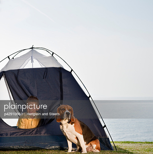 Boy with dog in tent by sea