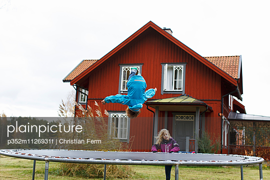 Sweden, Sodermanland, Jarna, Boy (6-7) and girl (10-11) jumping on and climbing trampoline