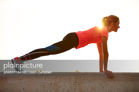 A young athletic woman working out outdoors.