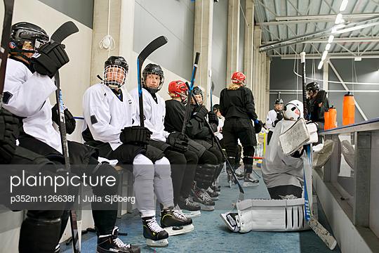 Sweden, Young ice hockey players sitting on bench by ice rink waiting for game