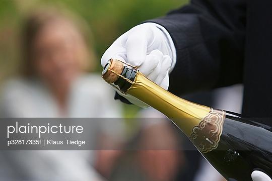 Waiter holding champagne bottle