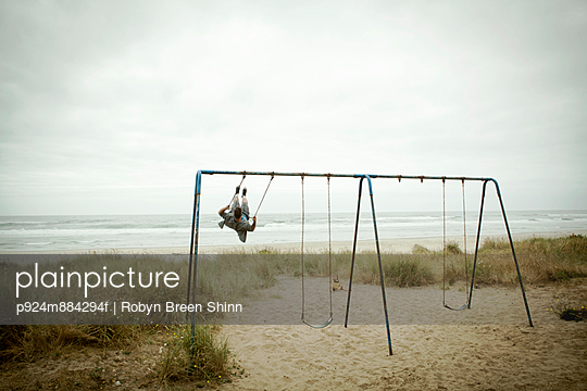 Female toddler watching father on beach swing