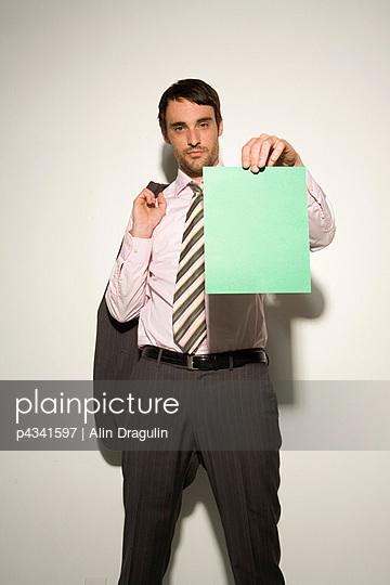 Businessman showing paper , portrait