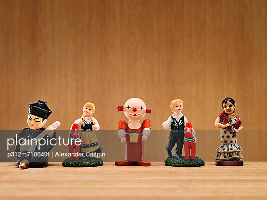 Small figurines on wooden background