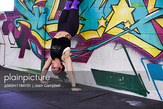 A female athlete trains in a crossfit gym.