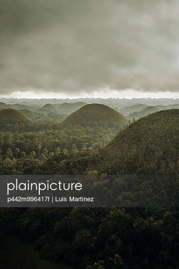 Chocolate hills landscape from Bohol Island, a big storm covers the sky making an interesting lighting effect; Carmen, Bohol Island, Philippines