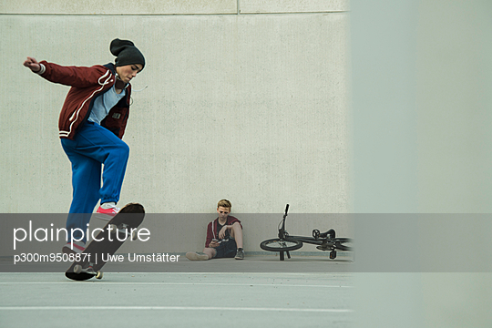 Two boys with BMX bike and skateboard on parking level