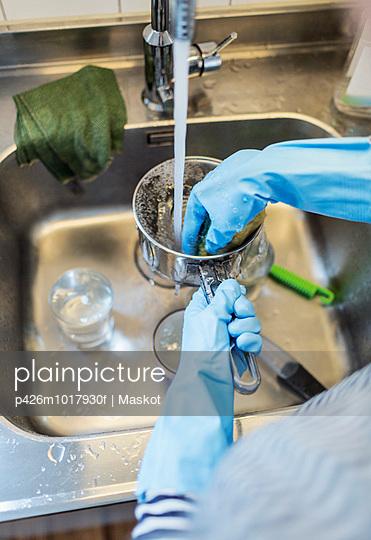Cropped image of woman washing sauce pan at sink in kitchen