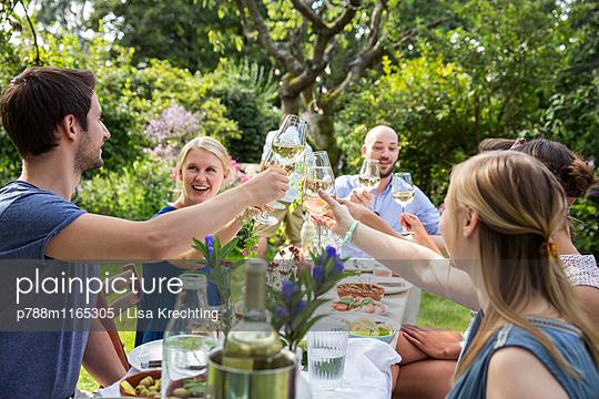 Freunde feiern eine Gartenparty - p788m1165305 von Lisa Krechting
