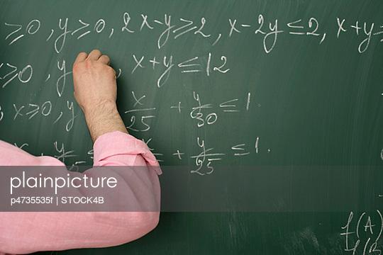 Teacher writing an arithmetic problem on blackboard