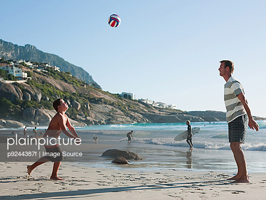 Father and son playing ball on a beach
