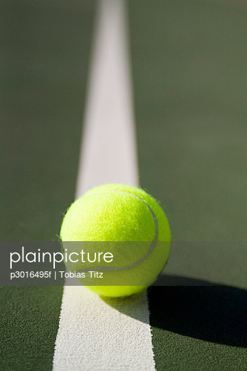 A tennis ball lying on a white line