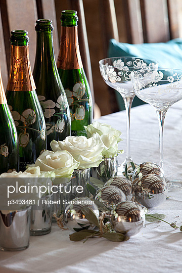 White roses and champagne bottles on table of Cotswolds home UK