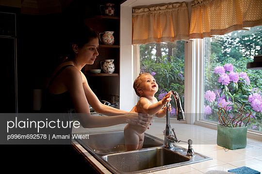 A Mother Gives Her Son A Bath In The Kitchen Sink.