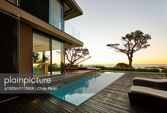 Modern luxury home showcase patio and swimming pool with sunset ocean view