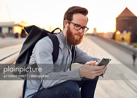 Mann mit Kopfhörern und Smartphone - p1124m1169977 von Willing-Holtz