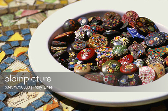 A dish of vintage decorated buttons on a mosaic table top