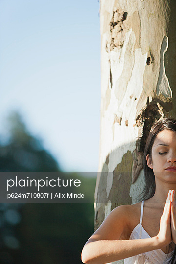 Young woman in prayer position, cropped
