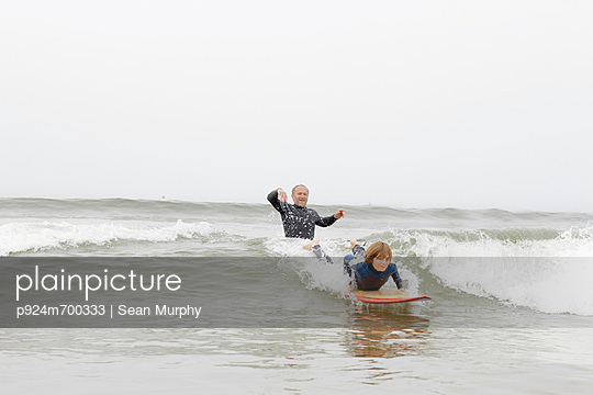 Surfing teacher and student in the sea