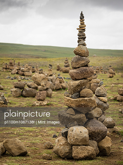 A tall rock cairn made by hikers to mark a spot on a walking path.