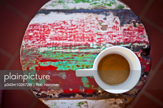 A cup of coffee sits on a colorful barstool.