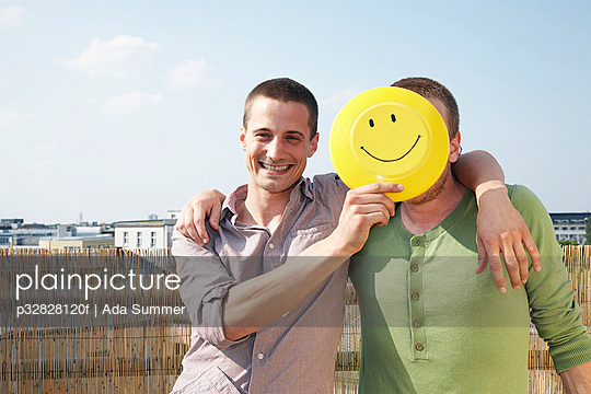 Man holding smiley face over friends face