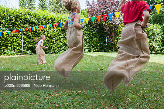 Children having a sack race in garden on a birthday party